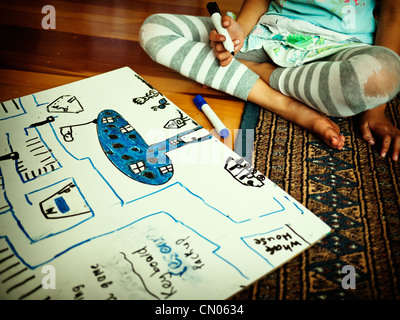 Girl draws map with pictures on whiteboard on floor - Stock Image