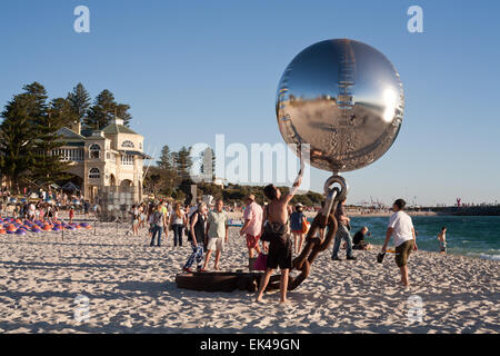 Man interacting with a large artwork at the 2015 Sculpture By The Sea event. Cottesloe beach, Perth. Western Australia - Stock Image
