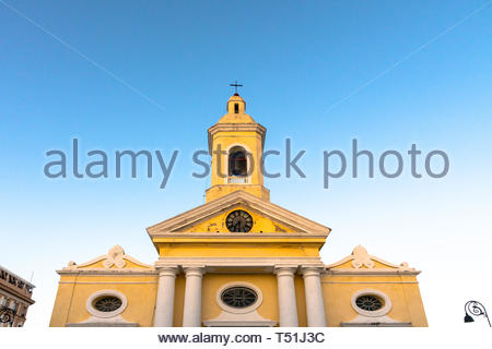 Facade of the colonial Roman Catholic Church in the city center. Low angle of the clock and bell tower. The place is a tourist attraction - Stock Image