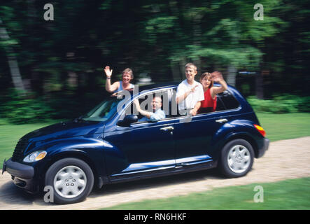 Family waving while driving in car, motion blur, USA - Stock Image