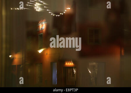 Reflections in a shop window. Swedish city on a icy winter night. - Stock Image