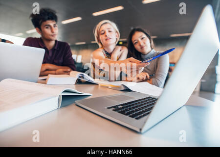 Multiracial young people doing group study at table with woman pointing at laptop. University students researching - Stock Image