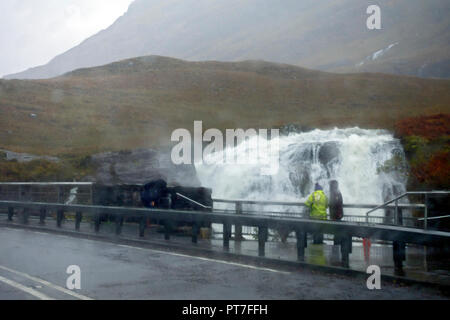 Scotland, UK. 7th Oct 2018. Tourists brave the weather to view the spectacular waterfall, enhanced by the torrential rain running off the mountains above, in Glencoe Scotland. Credit: PictureScotland/Alamy Live News - Stock Image