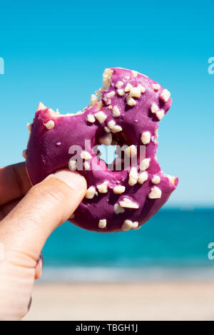 closeup of a nibbled appetizing donut, coated with a purple frosting and white sprinkles, in the hand of a young man against the blue sky, and the oce - Stock Image