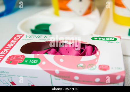 A box of pink tourniquets used while taking blood samples in a hospital treatment room. - Stock Image