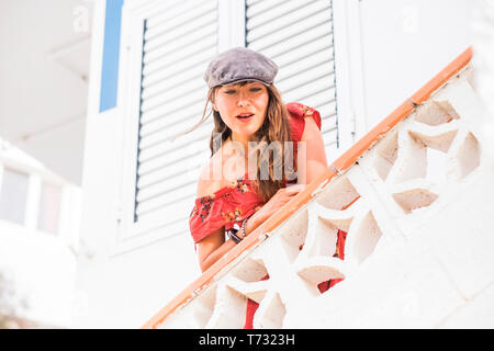 Fashion trendy young beautiful caucasian woman outside home with red dress and grey hat - smile and enjoying the leisure activity with white backgroun - Stock Image