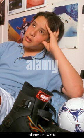 spaced out teenage boy sitting in his bedroom next to rollerblades - Stock Image