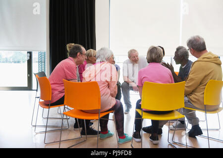 Active seniors talking in circle in community center - Stock Image
