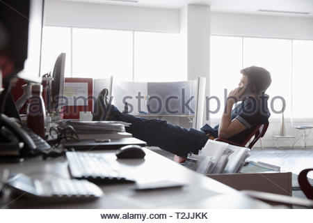 Businessman talking on smart phone with feet up on desk - Stock Image