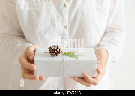 Young caucasian woman holds in hands gift box wrapped in white paper tied with twine pine cone juniper twig. Morning light pastel colors. Christmas Ne - Stock Image