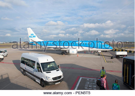 Schiphol Airport Amsterdam The Netherlands. An assistance bus arrives to take a disabled passenger to the terminal. Beyond a KLM Embraer ERJ-175STD PH - Stock Image