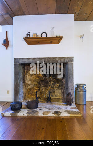 Fieldstone fireplace with cut stone contour, roughcast finish and black cast iron cooking pots in kitchen inside an old circa 1760 Canadiana home - Stock Image