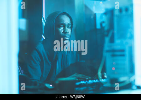 Serious tired black man in hoodie sitting in dark blue room and typing on computer keyboard while working on system software - Stock Image