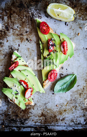 A simple and delicious avotoast with cherry tomatoes and tahini sauce. - Stock Image