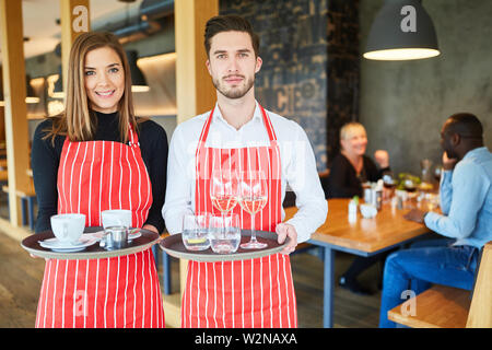 Husband and wife serving as a waiter team with tray in restaurant or bistro - Stock Image