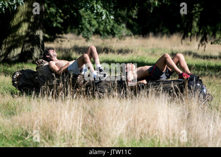 London, UK. 10th August, 2017. Two men sunbath in Hyde Park in London, UK as warm weather returns in the city. Credit: Ben Furst/Alamy Live News. - Stock Image