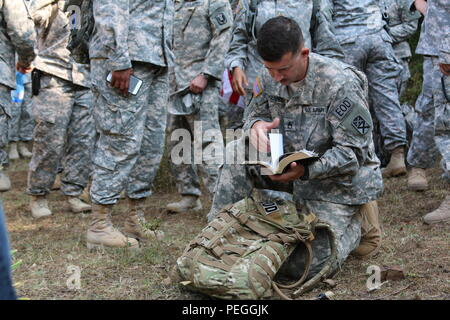 U.S. Army Staff Sgt. Brian Harris, an Alabama National Guard Soldier from the 666th Explosive Ordnance Company out of Jacksonville, Alabama, and currently assigned to Multinational Battle Group-East, reads his Bible during the Black Madonna Pilgrimage, Aug. 15, 2015, at the Church of the Black Madonna in Letnica, Kosovo. MNBG-East Soldiers have participated in the pilgrimage for the past decade, which honors the Catholic Feast of the Assumption of Mary. (U.S. Army photo by Ardian Nrecaj, Multinational Battle Group-East) - Stock Image