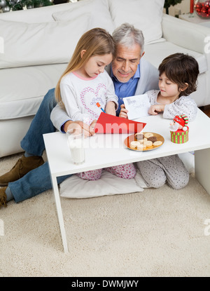 Man Assisting Children In Making Christmas Greeting Card - Stock Image