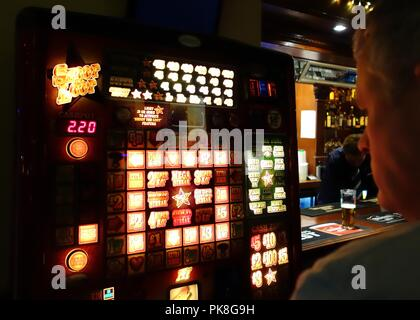 A man playing a gaming machine hoping to win a cash prize in a bar in Glasgow, Scotland, UK - Stock Image