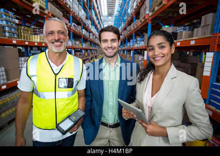 Portrait of warehouse team standing with digital tablet and barcode scanner - Stock Image