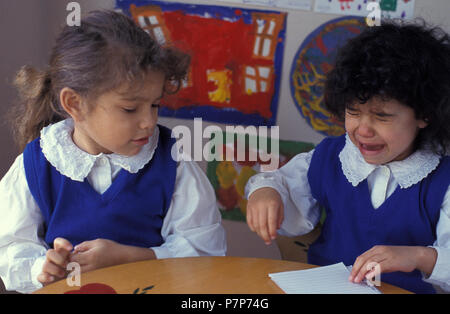 two primary school girls fighting at desk - Stock Image