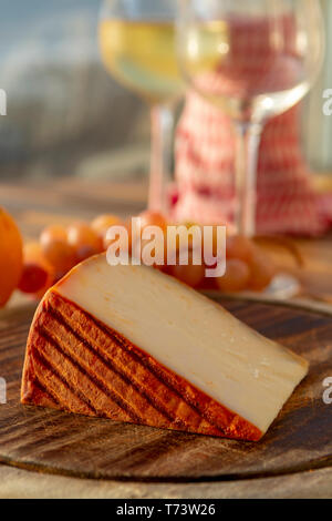 Spanish goat milk cheese with paprika coating and ripe pink table grapes served with white wine on outdoor terrace close up - Stock Image