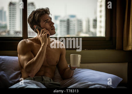 Naked young man with muscular body on bed with mug or cup in hand with coffee or tea talking on cell phone - Stock Image