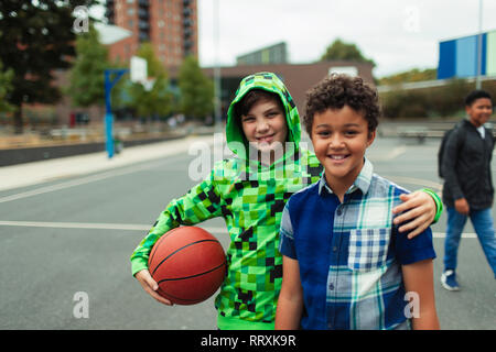 Portrait happy junior high boy friends playing basketball in schoolyard - Stock Image