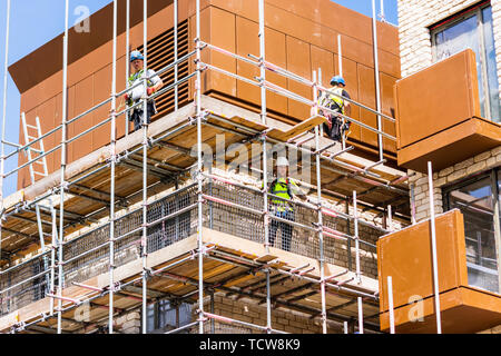 Construction workers in hard hats and hi viz safety clothing on scaffolding surround a new building being built - Stock Image