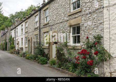 Row of old stone cottages adjacent to Litton Mill, Millers Dale, Derbyshire, UK; probably mill workers cottages but now in owner occupation. - Stock Image