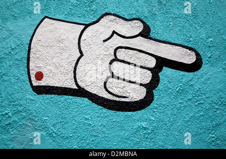 pointing hand painted on side of wall - Stock Image