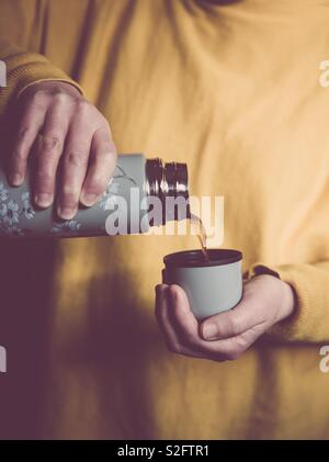 A mid section of a girl wearing yellow clothes and pouring hot coffee or tea from a thermos flask - Stock Image