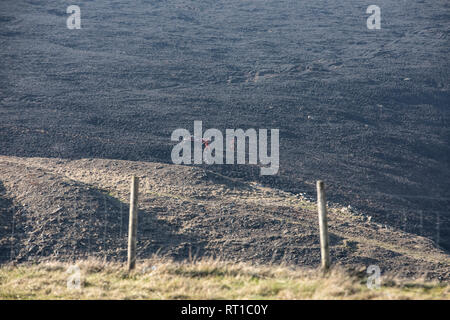 Marsden, UK. 27th Feb, 2019. Scorched moorland was still smouldering this afternoon following the dramatic fire overnight at Marsden Moor, near Saddleworth Moor. Firemen were using a special buggy, and breathing equipment, to survey areas of ground still smouldering. Credit: James Copeland/Alamy Live News - Stock Image