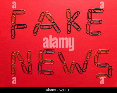 Fake News written in paper clips on a red background - Stock Image