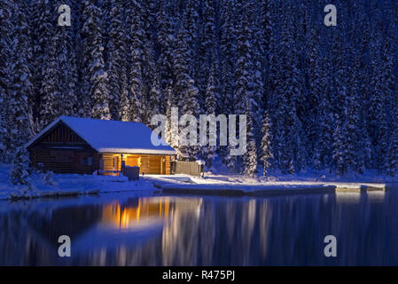 Lake Louise Canoe Rental Log Cabin reflected in Lake Louise Water on a Cold Winter Night in Banff National Park, Rocky Mountains Alberta Canada - Stock Image