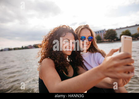 Shot of cheerful teenage girls smiling and taking selfie with smart phone by the lake. Female friends taking self - Stock Image