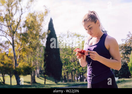attractive blonde sports woman touching phone screen before her training outdoors at park, fitness accessories - Stock Image