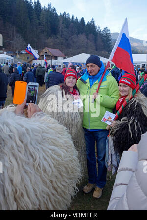 Borut Pahor the President of Slovenia posing with national flag to be photographed with women in carnival 'kurent - Stock Image