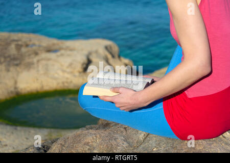 closeup of a woman reading a paperback book by the sea in the sun - Stock Image