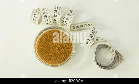 Brown sugar in a small transparent glass bawl and a curled measuring tape in centimeters beside it against a white background - Stock Image