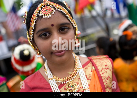 An East Indian or Hindu girl wearing traditional dress and headdress at a festival. - Stock Image