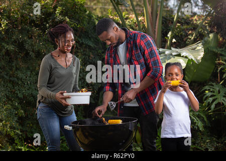 A family barbecuing food together - Stock Image