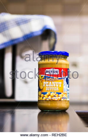 Poznan, Poland - November 20, 2018: Mcennedy Smooth peanut butter in a glass jar standing on a table with microwave in soft focus background. - Stock Image