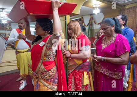 At her mother's thanksgiving service a Hindu woman brings offerings to the deities at a temple in Ozone Park, Queens, New York City. - Stock Image