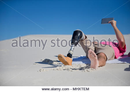 Man With Artificial Leg Lying On Sand And Looking At Digital Tablet On Beach Vacation - Stock Image