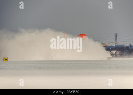 easyJet Airbus A319 plane disappearing in a cloud of snow as it takes off from London Southend Airport departing for Alicante. Snow covered airport - Stock Image