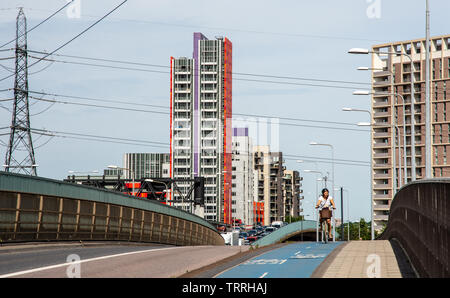 London, England, UK - June 1, 2019: A cyclist rides along Cycle Superhighway 3 past new build high rise apartment buildings in the Canning Town neighb - Stock Image