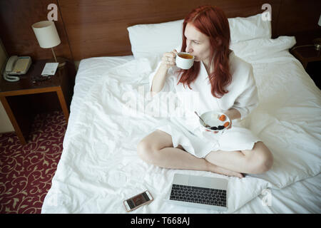A ginger woman sitting on the bed and drinking tea - Stock Image