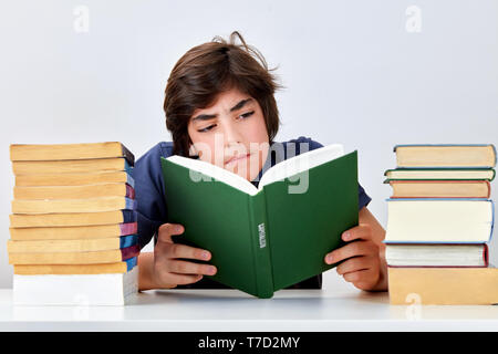 Teenage kid with serious concentrated expression sitting at the desk between pile of books and reading a book on capitalism - Stock Image