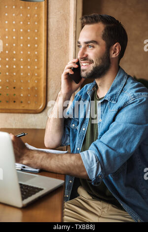 Photo of handsome smiling man wearing denim shirt talking on cellphone with laptop and clipboard while working in cafe indoors - Stock Image